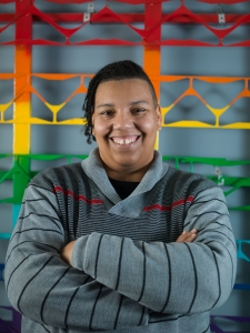 A non-binary person smiling in front of a rainbow structure